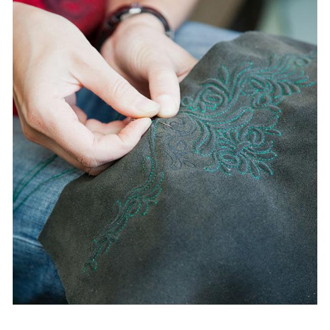 Die Teile der Lederhose werden von Hand bestickt