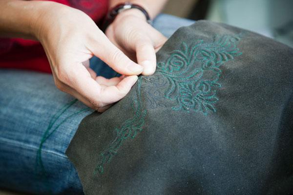 So wird eine Lederhose von Hand bestickt